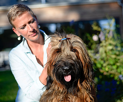 Portrait of dog with hair clip with owner in the background - p300m2058652 by Bernd Friedel