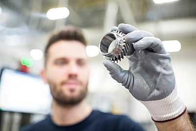 Close-up of man holding workpiece in a factory - p300m2245995 by Westend61