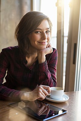 Portrait of mid adult woman with coffee and digital tablet at cafe table - p429m1107062f by Philipp Nemenz