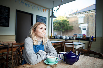 Young woman sitting in cafe, cup of tea and teapot on table, thoughtful expression - p429m1206911 by Janeycakes Photos