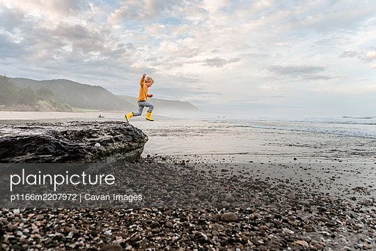 Young curly haired child leaping from rock at beach in New Zealand - p1166m2207972 by Cavan Images
