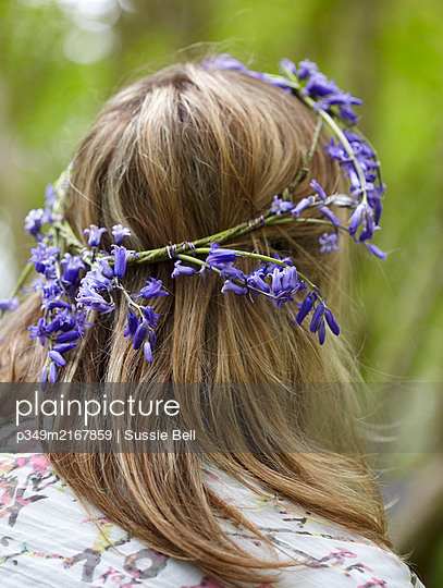 Woman wears bluebell garland in hair  (Hyacinthoides non-scripta). - p349m2167859 by Sussie Bell