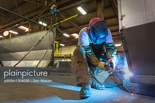 Caucasian man welding metal in factory - p555m1304035 by Don Mason