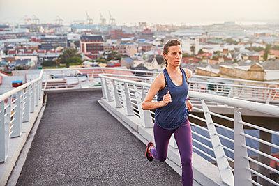 Female runner running on urban footbridge - p1023m1201841 by Ryan Lees