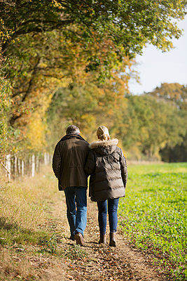 Affectionate mature couple walking in sunny, rural autumn field - p1023m2010358 by Sam Edwards