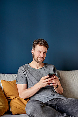 Young man writing short message on smartphone - p1124m1589426 by Willing-Holtz