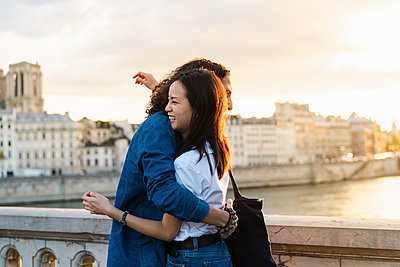France, Paris, happy young couple hugging at river Seine at sunset - p300m2024050 by VITTA GALLERY
