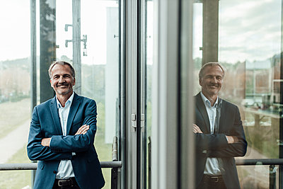 Smiling male business professional with arms crossed standing against window in office - p300m2266298 by Gustafsson