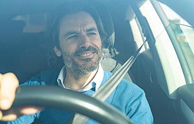 Mature male entrepreneur smiling while driving car - p300m2282160 by Jose Carlos Ichiro