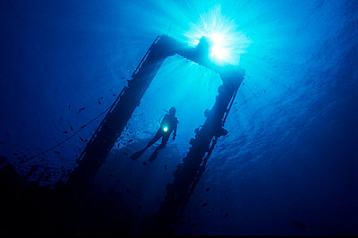 Underwater photography of a silhouetted diver from behind the door frame structure of a sunken ship - p3485701 by Kimmo Hagman