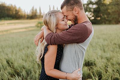 Romantic man and girlfriend hugging in field of long grass - p924m2039576 by Sara Monika