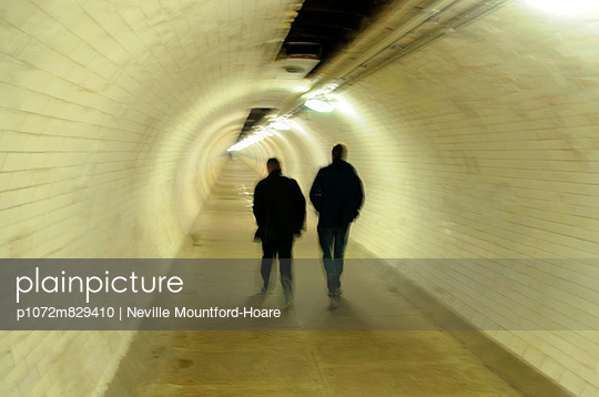 Two blurred men walking through foot tunnel - p1072m829410 by Neville Mountford-Hoare