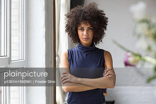 Hübsche Geschäftsfrau mit Afro steht neben einem Fenster und verschränkt ihre Arme  - p1301m1582961 von Delia Baum
