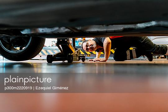 Male mechanic examining car tire in auto repair shop - p300m2220919 by Ezequiel Giménez