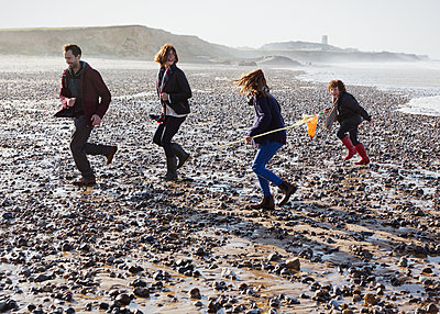 Family running on rocky beach - p1023m1106081f by Sam Edwards