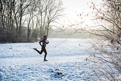 Young woman jogging in winter landscape - p1026m1025121f by Patrick Frost