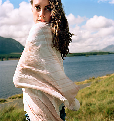 Portrait of confident young woman wrapped in scarf standing on lakeshore - p1166m1163335 by Cavan Images
