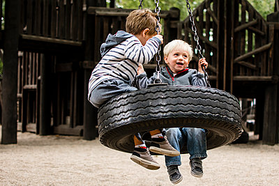 Happy brothers swinging in playground - p1166m1186029 by Cavan Images