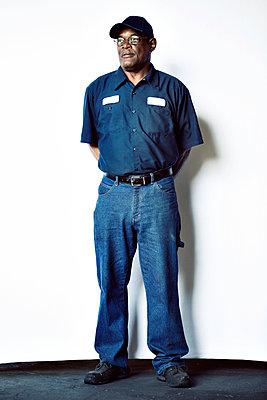 Full length of senior worker standing against white backdrop - p1166m1526786 by Cavan Images