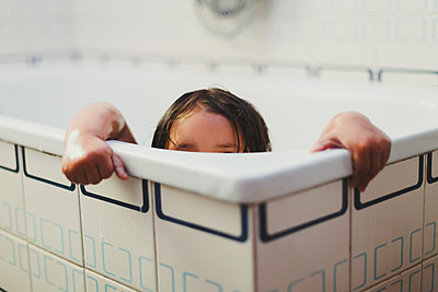 Little girl showering in the bathtub, hands clutching bathtub and head - p1166m2147187 by Cavan Images