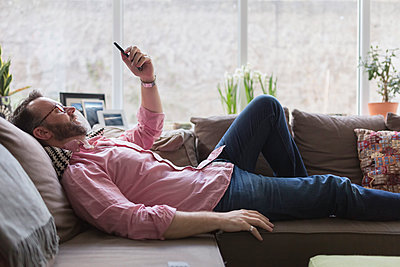 Mature man lying on couch taking selfie - p300m1140819 by Boy photography