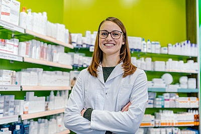 Portrait of smiling pharmacist at shelf with medicine in pharmacy - p300m1549783 by Mareen Fischinger