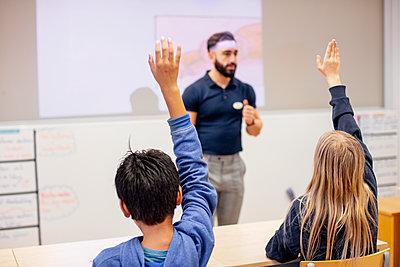 Children raising hands in classroom - p312m2191090 by Scandinav
