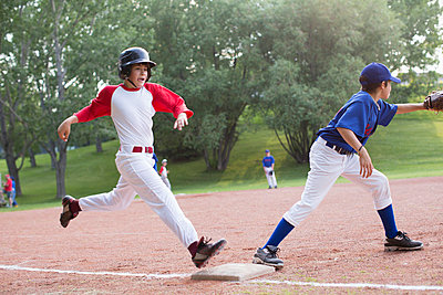 Young baseball player running for first base. - p328m783931f by Hero Images