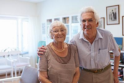 Portrait of senior couple standing arm around in nursing home - p426m2072527 by Kentaroo Tryman
