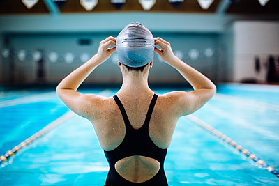 Rear view of woman by swimming pool putting on swimming cap - p429m1174988 by Sofie Delauw
