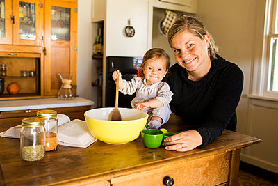 Caucasian mother and baby girl baking in kitchen - p555m1411630 by Adam Hester