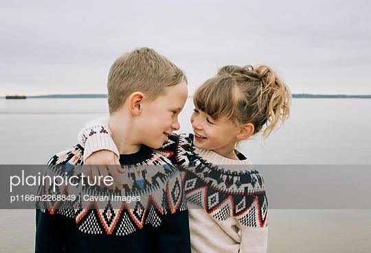 brother and sister hugging and smiling together at the beach in the UK - p1166m2268849 by Cavan Images