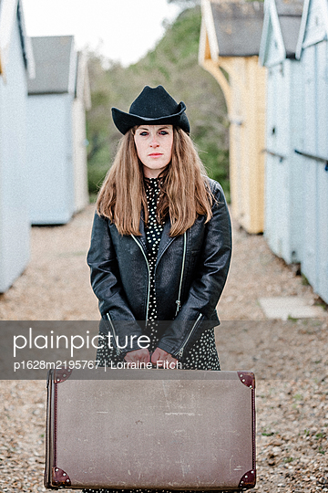 Woman with brown hair, long dress, cowboy hat, holding a suitcase - p1628m2195767 by Lorraine Fitch