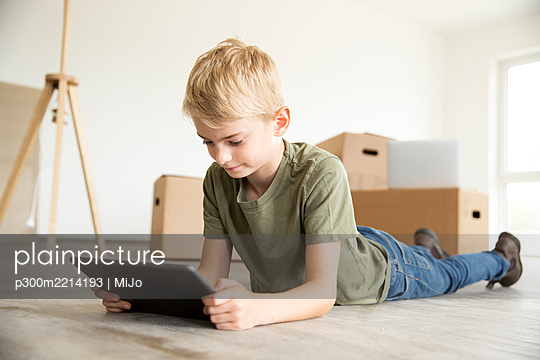 Boy with blond hair using digital tablet while lying on floor in new house - p300m2214193 by MiJo