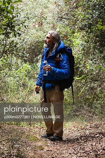 Male explorer holding water bottle while looking at plants in forest during weekend - p300m2277361 by NOVELLIMAGE