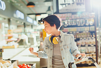 Young woman with headphones browsing, grocery shopping in market - p1023m1485627 by Tom Merton