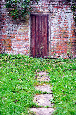 Pathway leading to old wooden door - p1047m789471 by Sally Mundy