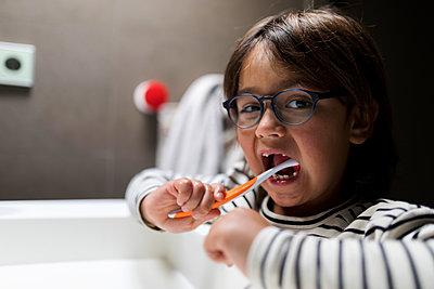 Boy on striped top Brushing His Teeth - p1166m2096398 by Cavan Images