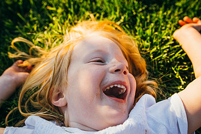 Close Portrait Of Little Girl Laughing and Laying in the Grass - p1238m1042073 by Amanda Voelker