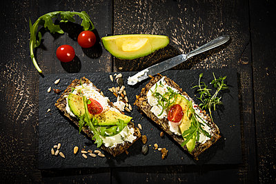 Onion bread with cream cheese, parma ham, avocado, rucola, thyme and tomato - p300m1587216 by Roman Märzinger