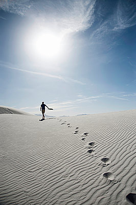 Young man walking across sand dune - p429m898319 by Lindsay Upson