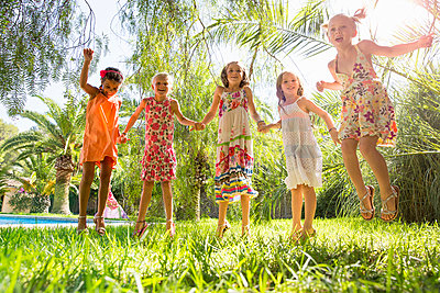 Five girls energetic girls jumping in garden - p429m974390f by RUSS ROHDE