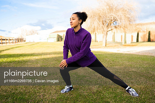 African American woman stretching and warming up before workout - p1166m2269735 by Cavan Images