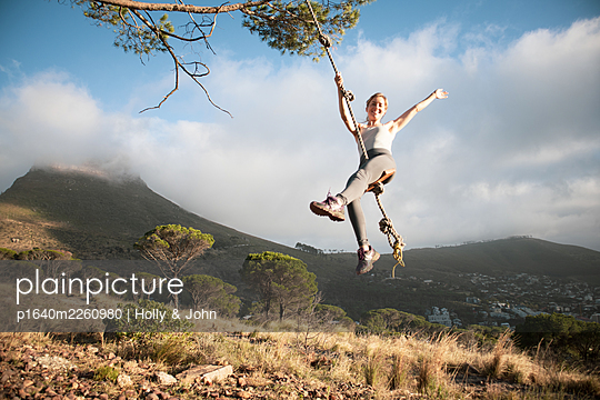 Sporty woman swings on rope, mountain range in background - p1640m2260980 by Holly & John