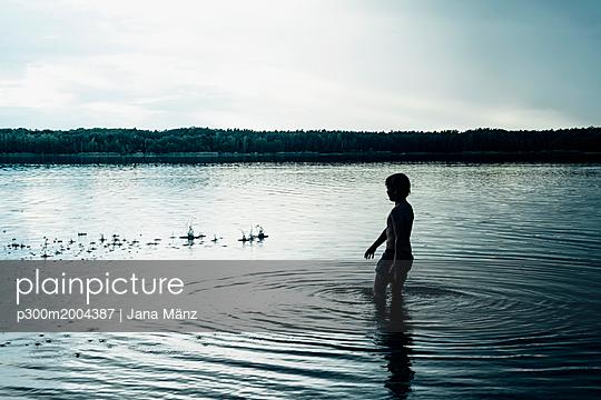 Boy in a lake at dusk - p300m2004387 von Jana Mänz
