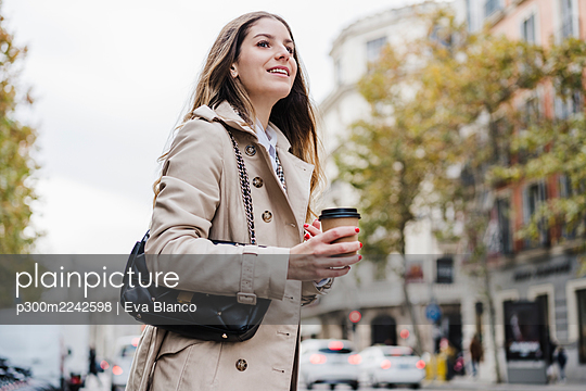 Smiling woman holding disposable coffee cup while looking away on street in city - p300m2242598 by Eva Blanco