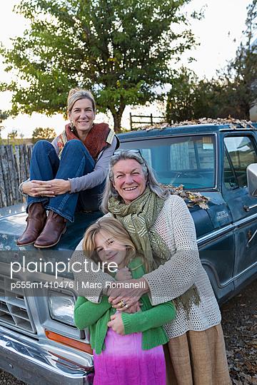 Three generations of Caucasian women sitting on truck - p555m1410476 by Marc Romanelli