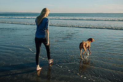Rear view of woman walking with dog toward sea against sky on shore - p1166m1508264 by Cavan Images
