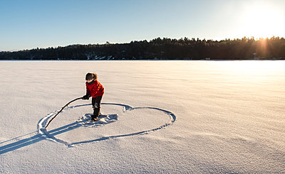 Child drawing a heart shape in an open snowy field in the morning sun. - p1166m2255302 by Cavan Images