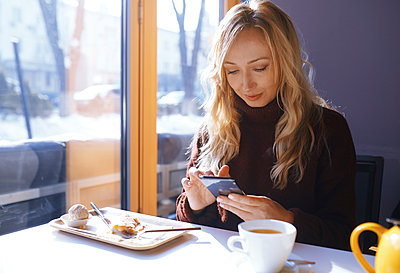 Woman text messaging during breakfast at restaurant - p1427m2067236 by Arman Zhenikeyev